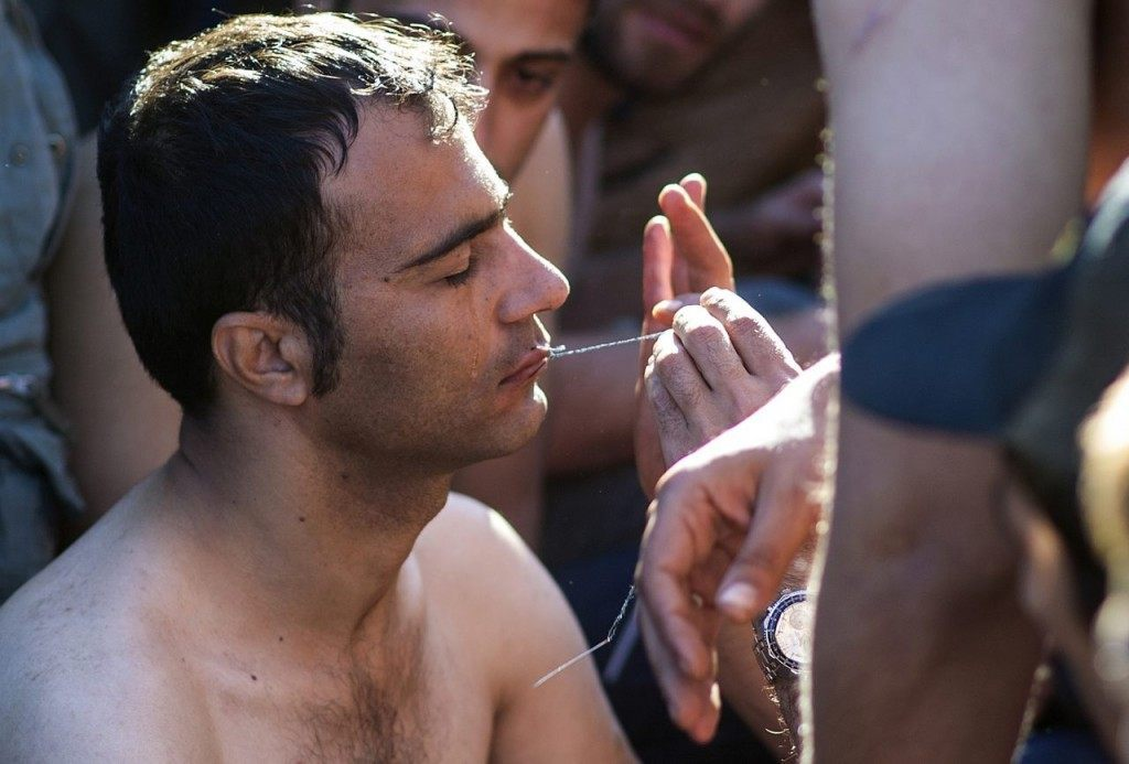 A man sews shut the mouth of a migrant or refugee who claimed to be from Iran as migrants and refugees wait to cross the Greek-Macedonian border near Gevgelija on November 23, 2015. At least five migrants stuck on the Greek-Macedonian border on November 23 sewed their lips in protest at not being allowed to continue their journey to Europe, AFP reporters said. The men, who say they are from Iran and threaten to go on hunger strike, have been camping on the tracks of the railroad between the two countries since November 20. / AFP / ROBERT ATANASOVSKI (Photo credit should read ROBERT ATANASOVSKI/AFP/Getty Images)