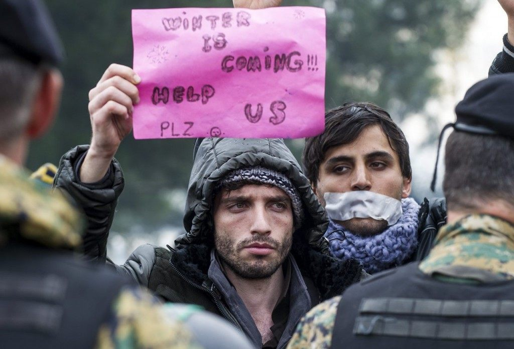 A man holds a placard reading 'Winter is coming' during a demonstration of migrants waiting to cross the Greek-Macedonian border demonstrate near Gevgelija, on November 25, 2015. Since last week, Macedonia has restricted passage to northern Europe to only Syrians, Iraqis and Afghans who are considered war refugees. All other nationalities are deemed economic migrants and told to turn back. Over 1,500 people are stuck on the border, mostly Indians, Moroccans, Bangladeshis and Pakistanis. / AFP / ROBERT ATANASOVSKI (Photo credit should read ROBERT ATANASOVSKI/AFP/Getty Images)