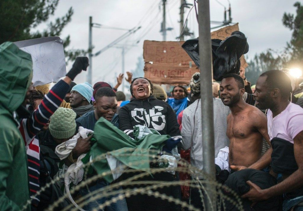 Migrants from Congo dance during a demonstration near Gevgelija, on November 25, 2015, as they wait to cross the Greek-Macedonian border. Since last week, Macedonia has restricted passage to northern Europe to only Syrians, Iraqis and Afghans who are considered war refugees. All other nationalities are deemed economic migrants and told to turn back. Over 1,500 people are stuck on the border, mostly Indian, Moroccan, Bangladeshi and Pakistani. AFP PHOTO / ROBERT ATANASOVSKI / AFP / ROBERT ATANASOVSKI (Photo credit should read ROBERT ATANASOVSKI/AFP/Getty Images)