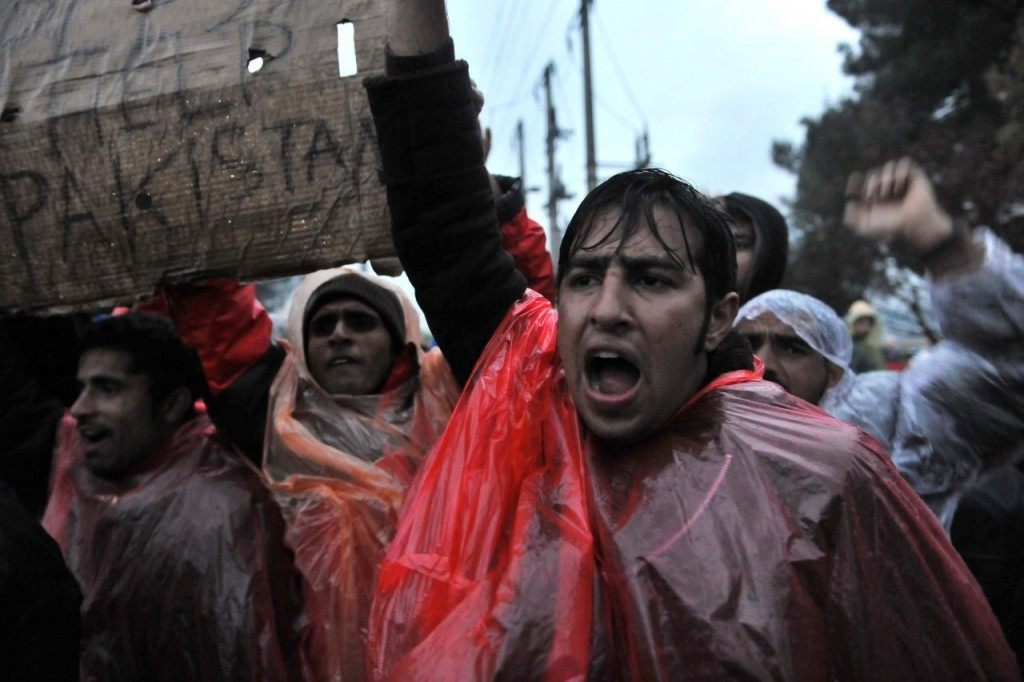 Migrants and refugees from Pakistan demonstrate in the rain as they wait to cross the Greek-Macedonian border near Idomeni on November 25, 2015. Since last week, Macedonia has restricted passage to northern Europe to only Syrians, Iraqis and Afghans who are considered war refugees. All other nationalities are deemed economic migrants and told to turn back. Over 1,500 people are stuck on the border, mostly Indians, Moroccans, Bangladeshis and Pakistanis. AFP PHOTO / SAKIS MITROLIDIS / AFP / SAKIS MITROLIDIS (Photo credit should read SAKIS MITROLIDIS/AFP/Getty Images)