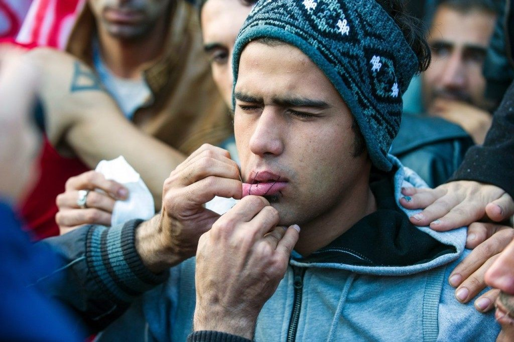 A man uses needle and thread to sew shut the mouth of a compatriot from Iran as a sign of protest as migrants and refugees wait to cross the Greek-Macedonian border near Gevgelija on November 26, 2015. Since last week, Macedonia has restricted passage to northern Europe to only Syrians, Iraqis and Afghans who are considered war refugees. All other nationalities are deemed economic migrants and told to turn back. Over 1,500 people are stuck on the border, mostly Indian, Moroccan, Bangladeshi and Pakistani. AFP PHOTO / ROBERT ATANASOVSKI / AFP / ROBERT ATANASOVSKI (Photo credit should read ROBERT ATANASOVSKI/AFP/Getty Images)