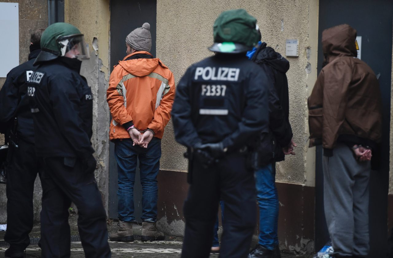 A migrant is handcuffed by police (ODD ANDERSEN/AFP/Getty Images)