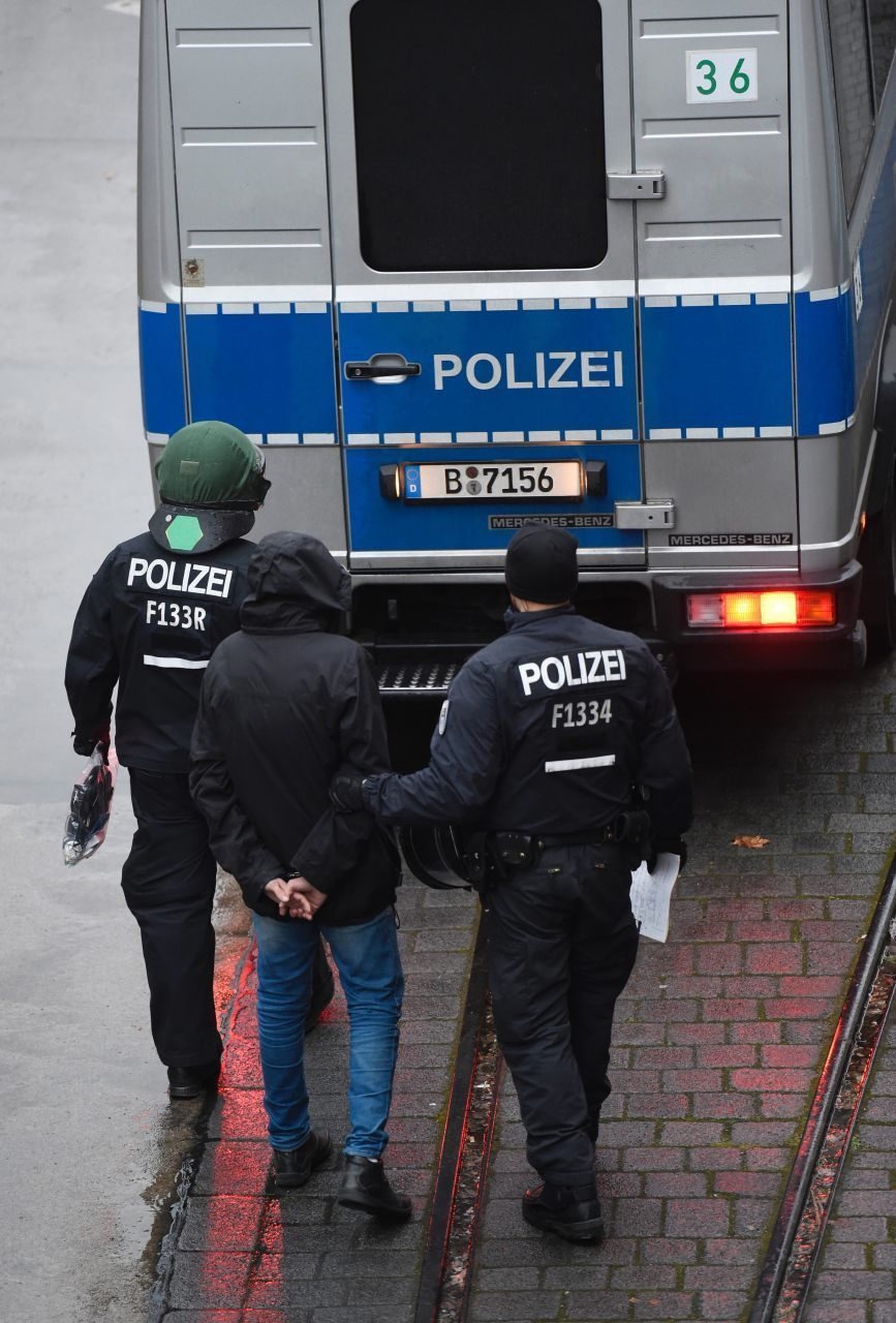 A migrant is arrested and escorted to a police van (ODD ANDERSEN/AFP/Getty Images)