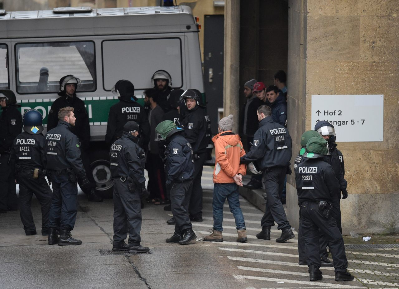Police escort a handcuffed migrant from the scene (ODD ANDERSEN/AFP/Getty Images)