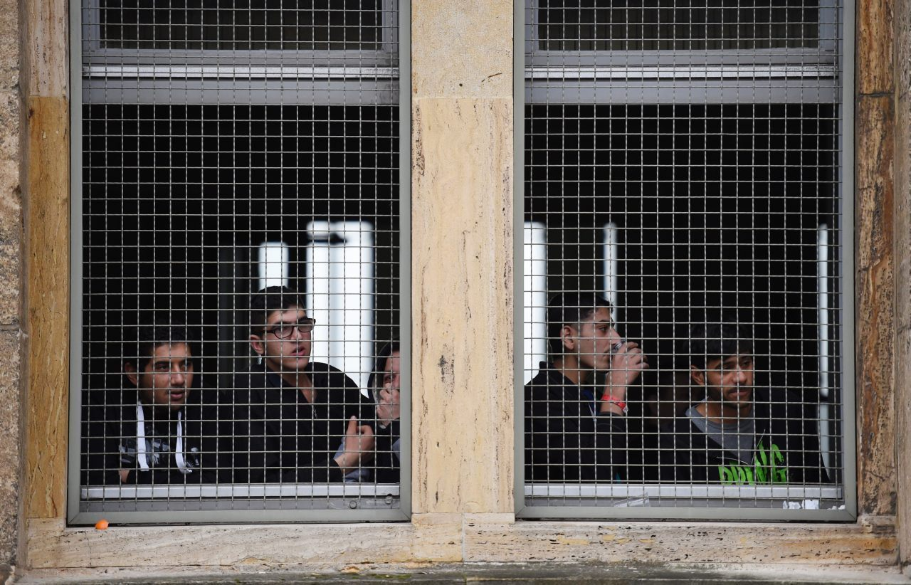 Migrants look out the window of the asylum centre (ODD ANDERSEN/AFP/Getty Images)