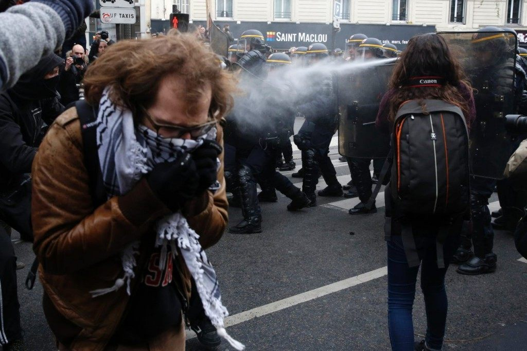 Riot police spray tear gas during clashes with protestors during a rally against global warming on November 29, 2015 in Paris, a day ahead of the start of UN conference on climate change COP21.