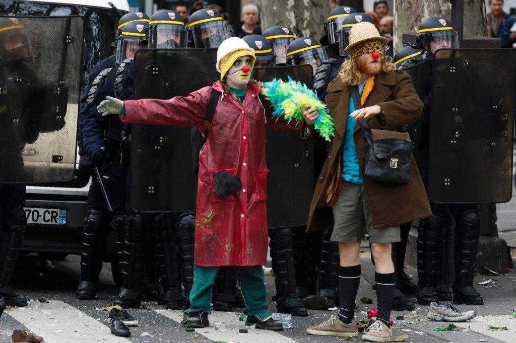 Protestors dressed as clowns stand in front of police as demonstrators clash with police during a rally against global warming on November 29, 2015 in Paris, a day ahead of the start of UN conference on climate change COP21.