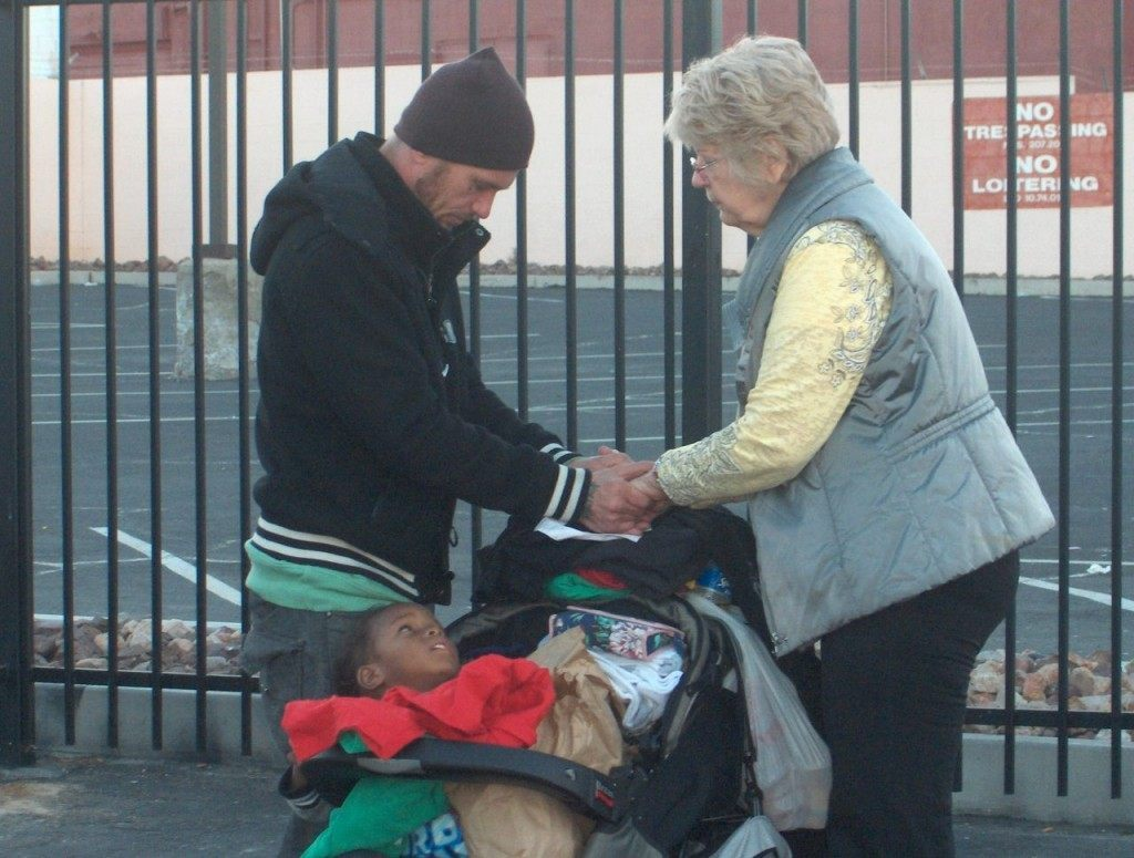 Bikers for Christ member pauses in prayer with a woman and child. (Photo: Pastor Leo Martinez)