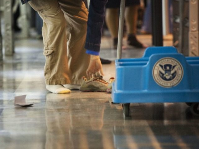A passenger removes their shoes before passing through the passenger security checkpoint at John F. Kennedy International Airport's Terminal 8 on October 22, 2010.
