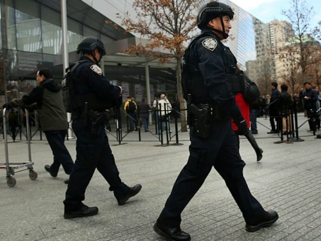 New York City police officers walk near One World Trade Center in lower Manhattan on November 24, 2015 in New York City. Following the terrorist attacks in Paris, security in New York City has been heightened throughout the metropolitan area as experts try to determine the nature of threats from …