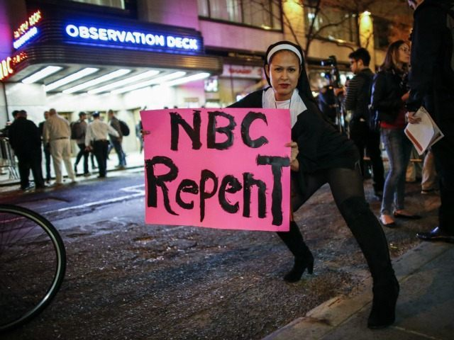 A woman dressed as nun holds a poster as she poses for a photo during a protest in front of NBC studios. (Kena Betancur/AFP/Getty Images)