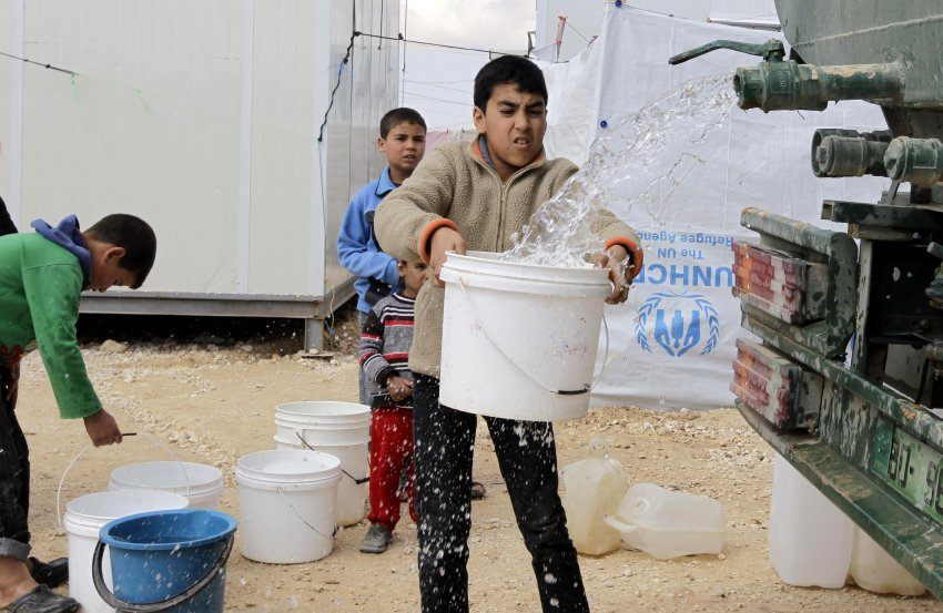 A picture taken on March 15, 2014 shows children collecting water from a truck at the sprawling desert Zaatari refugee camp in northern Jordan near the border with Syria which provides shelter to around 100,000 Syrian refugees. Syrian refugees in the seven-square-kilometre (2.8-square-mile) Zaatari camp   in Jordan fear that President Bashar al-Assad's likely re-election this year will leave their dream of a return home as distant as ever. The brutal war in Syria between the regime and its foes shows no sign of abating and has killed at least 146,000 people since it erupted in mid-March 2011. And 2.5 million Syrians have fled abroad and another 6.5 million have been internally displaced. Jordan is home to more than 500,000 of the refugees.  AFP PHOTO/KHALIL MAZRAAWI