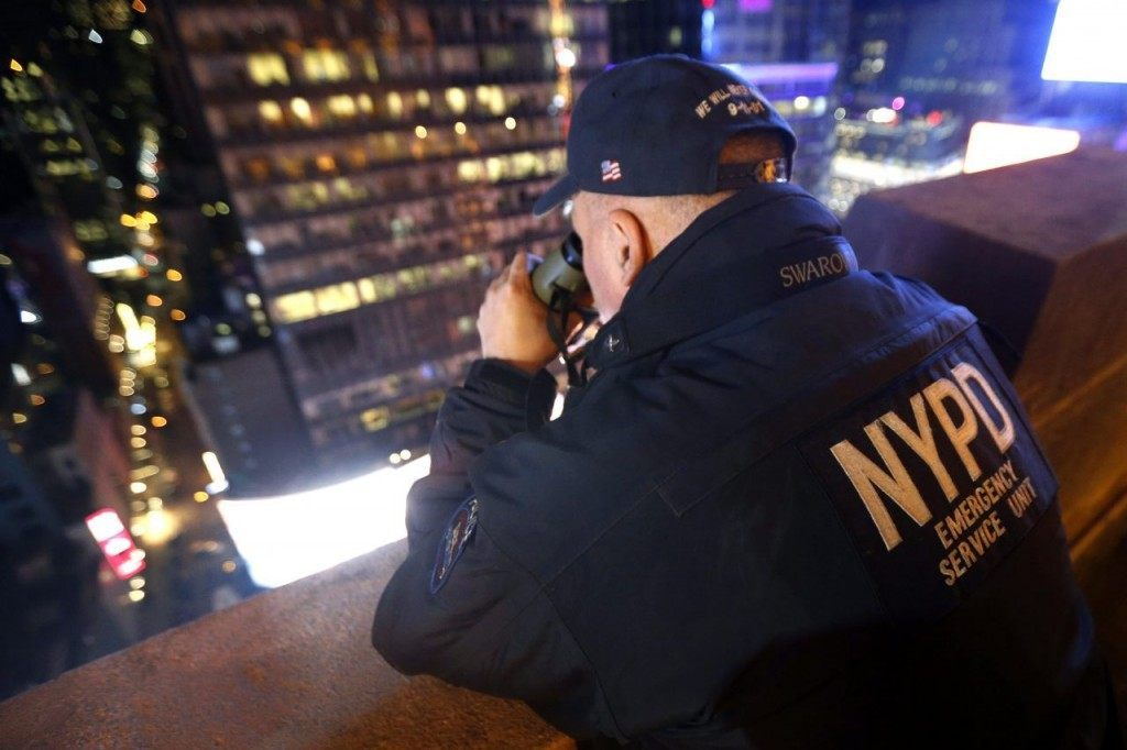 A New York police officer uses binoculars while keeping watch from a rooftop along Times Square during New Year's Eve celebrations, Thursday, Dec. 31, 2015, in New York. (AP Photo/Julio Cortez)