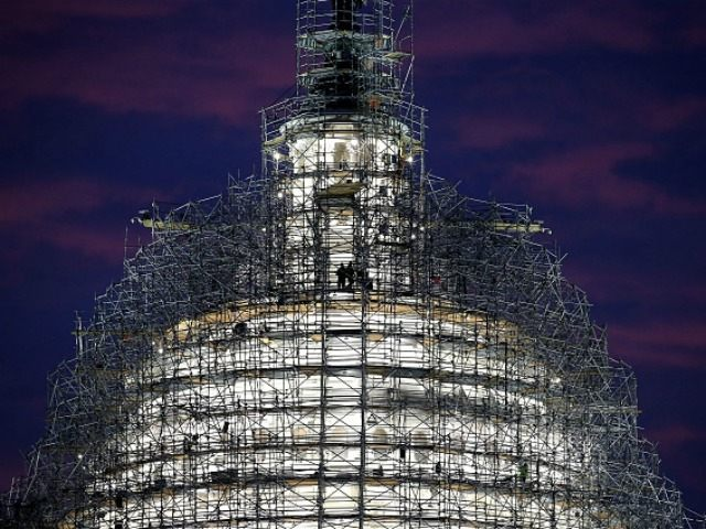 Workers stand on the scaffolding that surrounds the dome of the US Capitol which is undergoing restoration, November 17, 2015 in Washington, DC. The restoration of the cast iron dome is expected to take two years and cost as much as 60 million dollars (Photo by