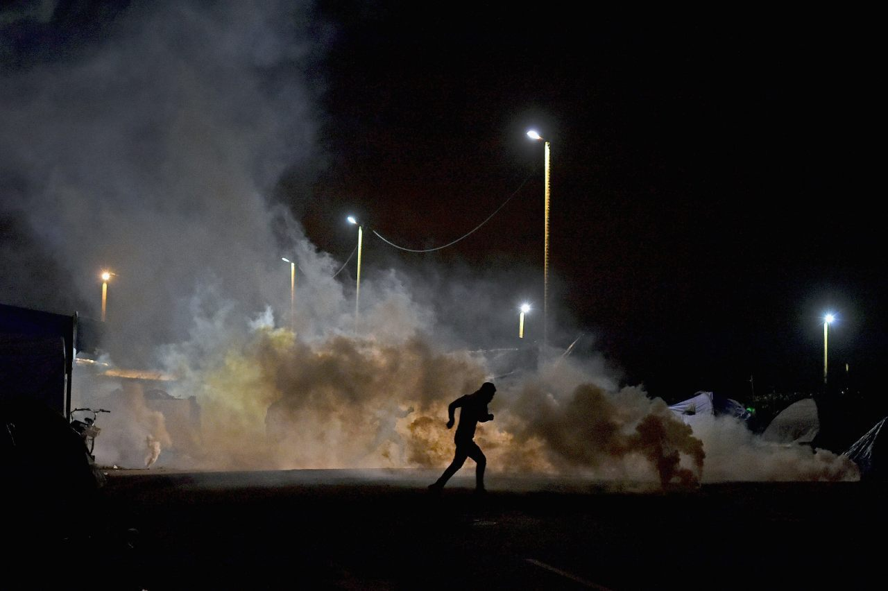 A migrant runs as police fire tear gas (Jeff J Mitchell/Getty Images)