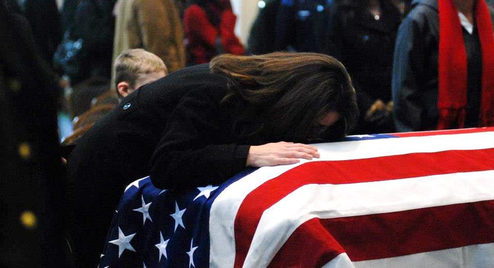 Kelly Terry-Willis weeps on the flag draping her brother's casket. (Photo: Facebook/Kelly Terry-Willis)