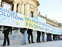 People display a banner reading which translates as 'false solutions COP21 No peace without climate justice' in front of the 'Solutions COP21' exhibition at the Grand Palais in Paris on December 4, 2015 as part of the COP 21, the United Nations conference on climate change. More than 150 world …