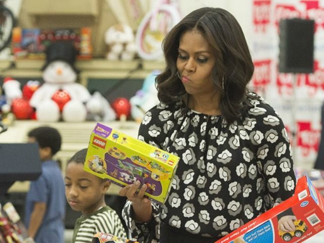First Lady Michelle Obama tries to decide which box to use as she sorts toys and gifts donated by the Executive Office of the President staff to the Marine Corps Reserve Toys for Tots Campaign by age at Joint Base Anacostia-Bolling in Washington, DC, December 9, 2015. AFP PHOTO / …