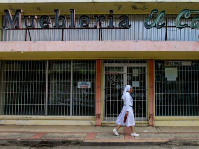 A nun walks in front of a closed furniture store in Lares, Puerto Rico, on September 2, 2015.