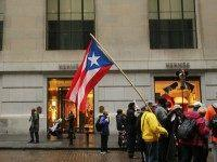 People protest outside of Wall Street against cutbacks and austerity measures forced onto the severely indebted island of Puerto Rico on December 2, 2015 in New York City. Puerto Rico made a $355 million payment on Tuesday on its bond debt to stave off a default. Officials have warned that …