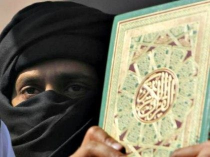 A supporter of a Pakistani religious party stands next to the Muslim holy book the Quran at a rally to condemn the reported burning of Qurans in Afghanistan by U.S. troops, in Lahore, Pakistan, on Friday, Feb 24, 2012. (AP Photo/K.M.Chaudary)