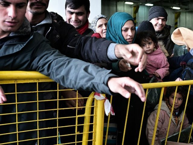Refugees and migrants wait for free blankets and raincoats before disembarking from a government chartered ferry 'El Venizelos' in the port of Piraeus near Athens on December 10, 2015. More than 4000 refugees arrived to the port from the Greek islands of Lesbos and Chios with the majority of them …