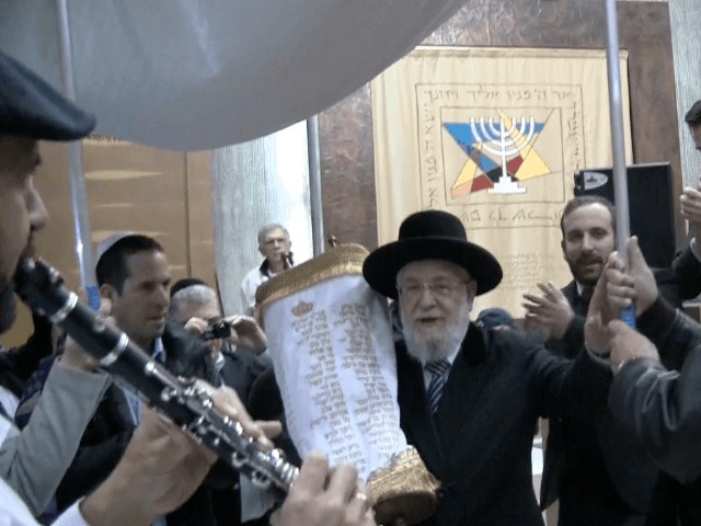 Rabbi Yisrael Meir Lau holding the new Torah scroll on which the names of the 72 soldiers killed in Operation Protective Edge are embroidered.