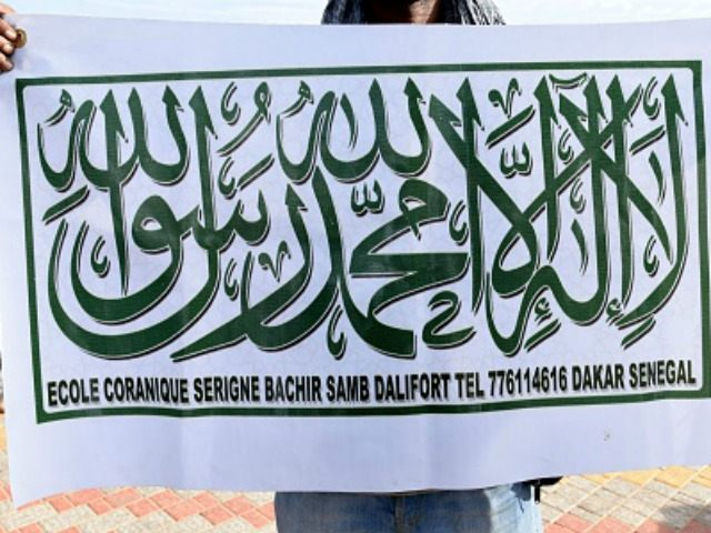 A demonstrator displays a banner featuring the Shahada (The Islamic creed stating a belief in one god and the acceptance that Mohammed was God's prophet) in Dakar on January 24, 2015 during a demonstration denouncing characatures featuring Mohammed published in the French satirical newspaper Charlie Hebdo. AFP PHOTO / SEYLLOU …
