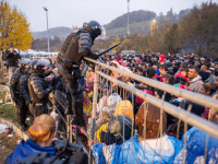A Slovenian policeman goes over a fence to rescue a child pushed by the crowd against the fence, as migrants and refugees wait to cross the Slovenian-Austrian border in Sentilj, Slovenia, to Spielfeld, Austria, on October 29, 2015.