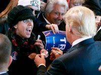 A campaign supporter reacts as Republican presidential candidate Donald Trump signs her button during a campaign event at the International Air Response facility on December 16, 2015 in Mesa, Arizona. Trump is in Arizona the day after the Republican Presidential Debate hosted by CNN in Las Vegas, Nevada. (Photo by …