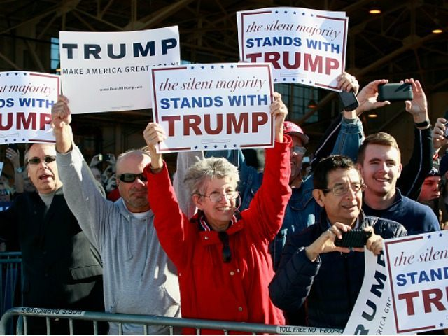 Campaign supporters hold up signs for Republican presidential candidate Donald Trump as his plane arrives to a campaign event at the International Air Response facility on December 16, 2015 in Mesa, Arizona. Trump is in Arizona the day after the Republican Presidential Debate hosted by CNN in Las Vegas, Nevada. …