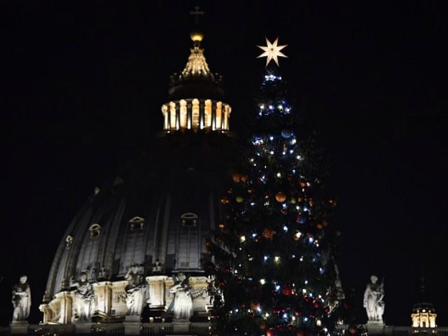 cupola of St Peter's basilica and the Christmas tree after its illumination on December 18, 2015 in Vatican. AFP PHOTO / GABRIEL BOUYS / AFP / GABRIEL BOUYS (Photo credit should read