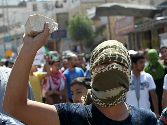 Palestinian protester holds a stone during clashes with Israeli security forces following an anti-Israeli protest after the weekly Friday prayers on September 18, 2015 in the Israeli-controlled area called H2, in the West Bank town of Hebron, after Hamas called for a 'day of rage' following three days of clashes around Jerusalem's Al-Aqsa mosque compound Islam's third holiest site, which is also considered the holiest site in Judaism and known to Jews as Temple Mount. Palestinians fear Israel will seek to change rules governing the holy site, with far-right Jewish groups pushing for more access and even efforts by fringe organisations to erect a new temple. AFP PHOTO / HAZEM BADER (Photo credit should read