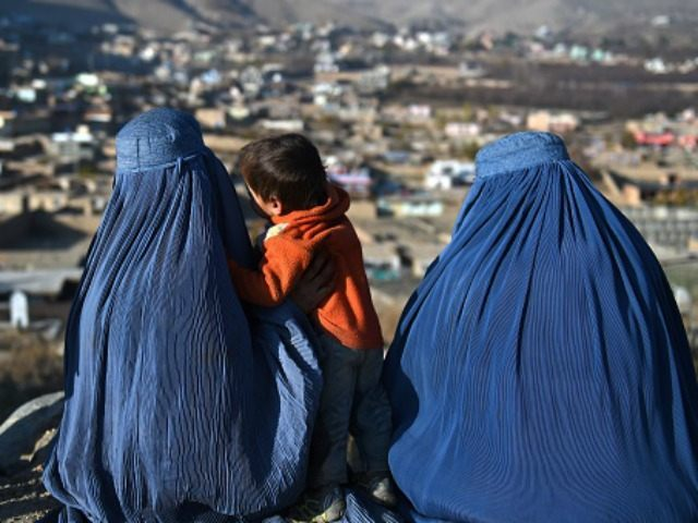 Afghan burqa clad women sit in a cemetery overlooking the outskirts of Kabul on December 1, 2015. AFP PHOTO / Wakil Kohsar / AFP / WAKIL KOHSAR (Photo credit should read