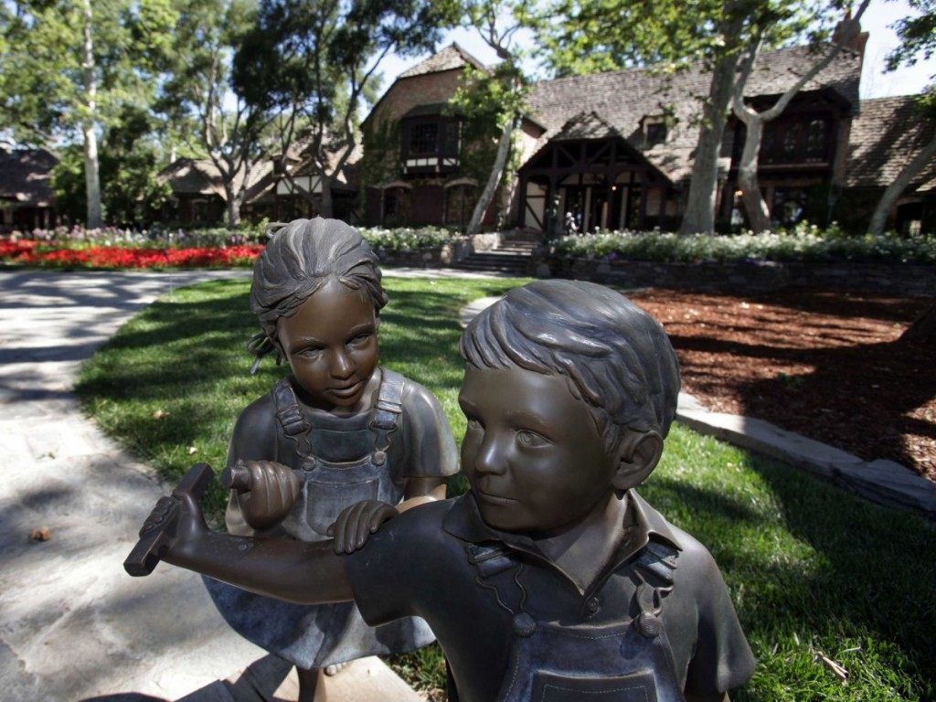 passing-through-the-gates-into-the-driveway-visitors-will-see-a-bronze-statue-of-children-playing-in-front-of-the-main-house