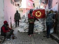"A flag of Kurdish workers Party ( PKK ) hangs on a barricade as armed kurdish militants man a barricade, on November 18, 2015 in the Sur district of Diyarbakir. Tensions rose when pro-Kurdish MP Leyla Zana began her oath with ""Biji Asiti"", or ""Long live peace"" in Kurdish. The phrase triggered a storm that recalled her memorable swearing-in 24 years ago when she also spoke the language that was then still taboo in public. AFP PHOTO/ILYAS AKENGIN"
