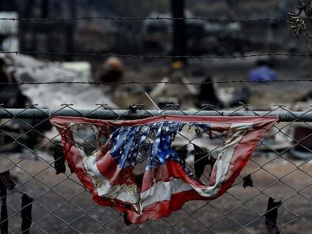 "A burnt US flag is pictured on a fence outside a damaged house as firefighters continue to battle the ""Valley Fire"" in the town of Cobb, California on September 15, 2015. Wildfires sweeping across California are threatening the US state's famed Sequoia trees, with firefighters scrambling to protect the national …"