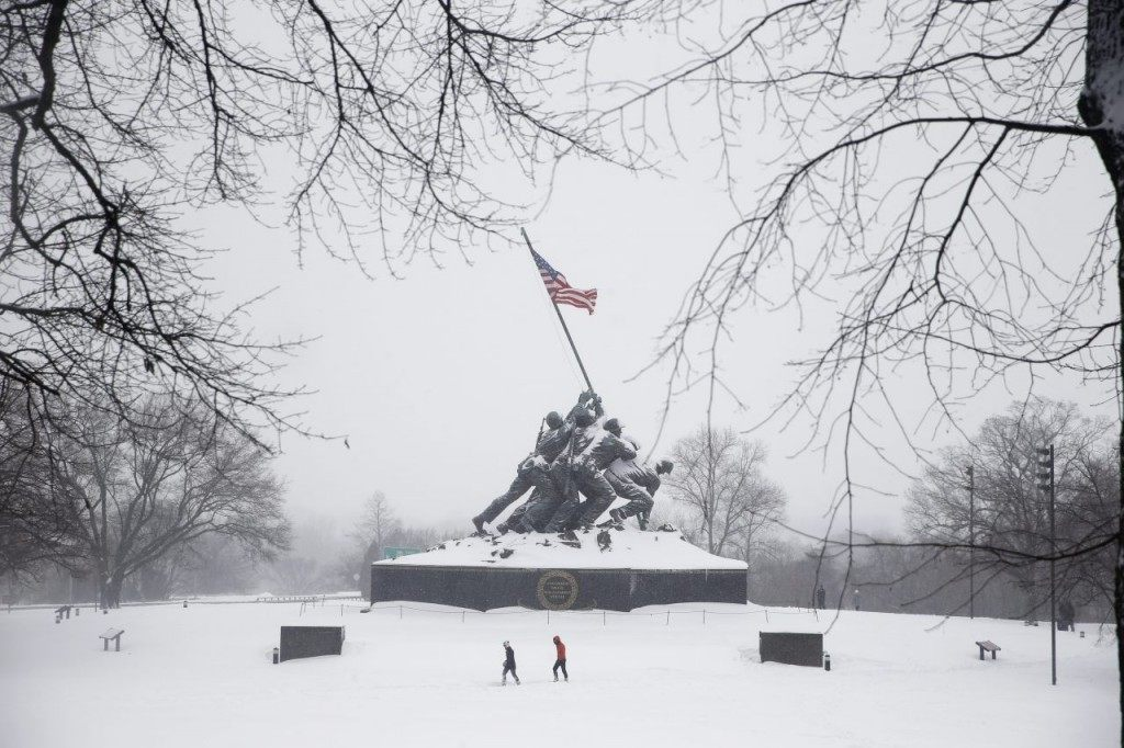 Two people make their way through the snow at The United States Marine Corps War Memorial, Saturday, Jan. 23, 2016 in Arlington, Va. (AP Photo/Alex Brandon)