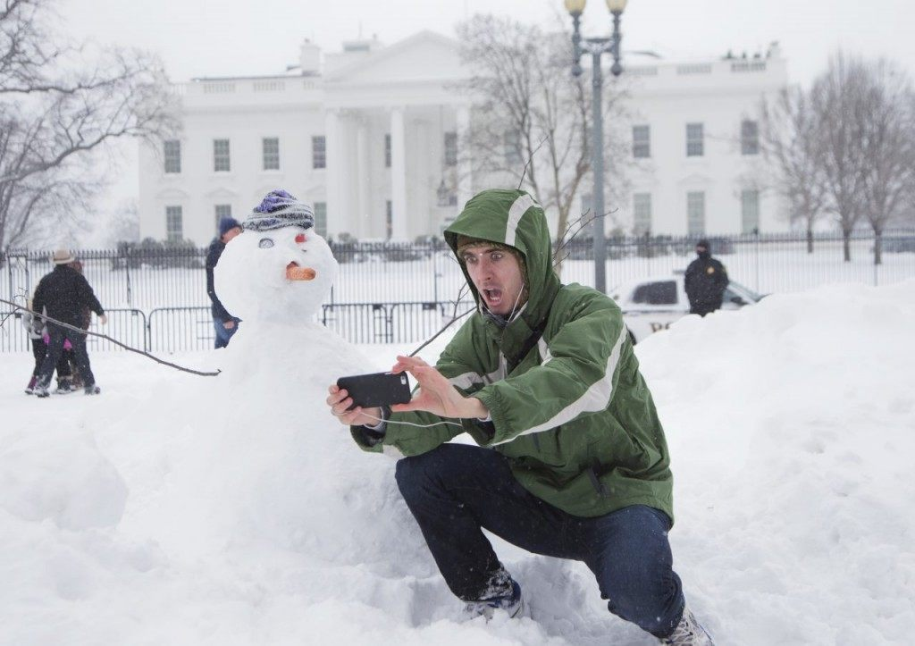 Harrison Feind of Boulder, Colo., takes a selfie with a snowman in front of the White House on Saturday. (AP Photo/Manuel Balce Ceneta)