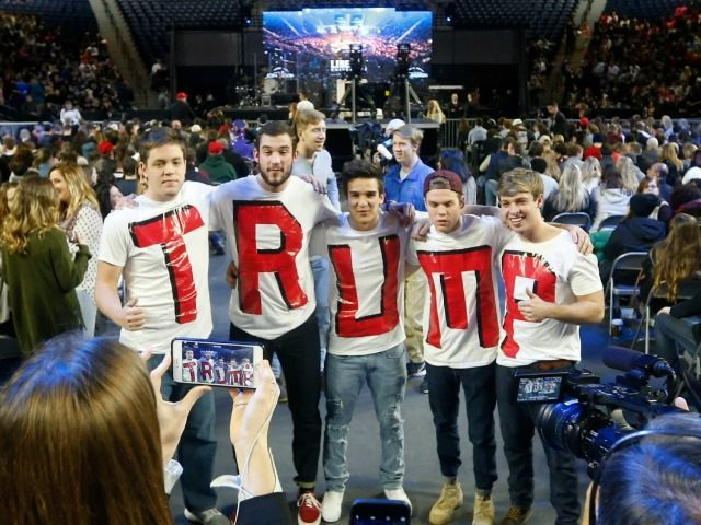 Liberty University students, Austin Miller, of Salisbury N.C., left, James Ford, of Elkton Md., second from left, Jeremy Boyd, of New York City, center, Josian O'Boyle, of Toronto Canada, second from right, and Cody Hildebrand, of Fayetteville W.Va., pose for photos with their home made t-shirts as they wait for …