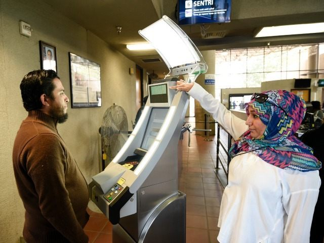 Contractor Sabira Dewji, right, helps a pedestrian crossing from Mexico into the United States at the Otay Mesa Port of Entry have his facial features and eyes scanned at a biometric kiosk Thursday, Dec. 10, 2015, in San Diego. On Thursday, U.S. Customs and Border Protection began capturing facial and …