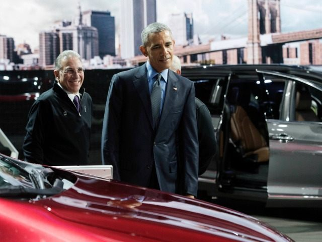 President Obama looks over the Chrysler Pacifica minivan, with NAIAS chairman Paul Sabatini at the North American International Auto Show in Detroit, Wednesday, Jan. 20, 2016.