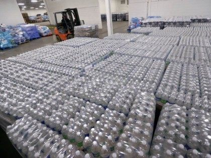 A forklift driver moves a pallet of water in a warehouse Tuesday, Jan. 19, 2016, in Flint, Mich. Area residents dealing with contaminated drinking water in Flint will be the recipients of the water, which they can pick up at fire stations throughout the city. (