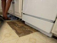 A leaky dishwasher has ruined a section of linoleum flooring.