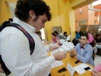 In this Tuesday, Oct. 6, 2015, photo, Alexander Haupt, left, 21, of Miami, looks over his job application as he speaks with Brooks Brothers Factory Store assistant store manager Daniel Lago, center, and visual merchandiser Barbie Pacheco, right, during a job fair at Dolphin Mall in Miami. The U.S. Labor …