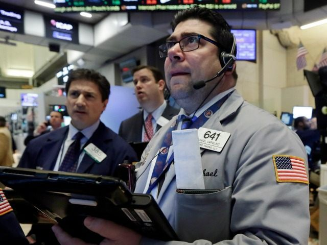 Michael Capolino, right, works with fellow traders on the floor of the New York Stock Exchange, Wednesday, Jan. 20, 2016. Energy stocks are leading another sell-off on Wall Street as the price of oil continues to plunge. (