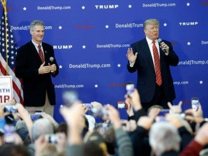 Former Massachusetts Sen. Scott Brown listens as Republican presidential candidate Donald Trump speaks during a campaign stop, Saturday, Jan. 16, 2016, in Portsmouth, N.H.
