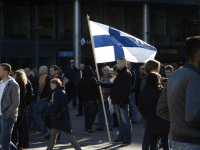 An anti-migration protesters holds a national flag on October 3, 2015 in Helsinki. Several protests, both pro- and anti-migration, were organized in cities of Finland.