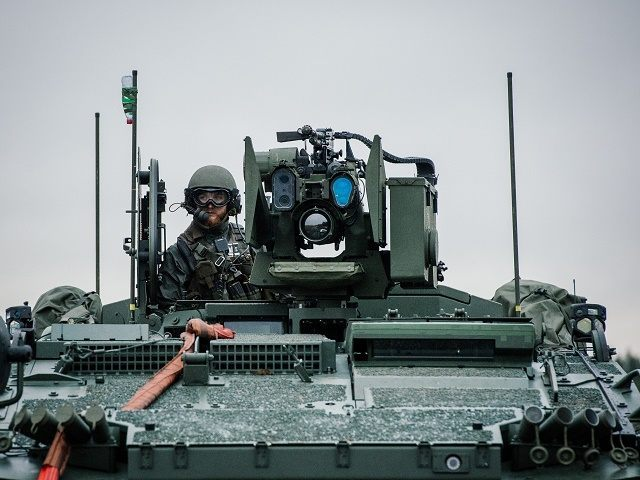 A soldier from the Swedish Armed Forces, looks on from top of the Patria XA-360 AMV (Armored Modular Vehicle) at Hagshult Airbase, part of the Forward Operation Base of the NBG about 240km North-East of Malmo, Sweden on November 6, 2014.The Nordic Battlegroup is one of European Union battlegroups. From …
