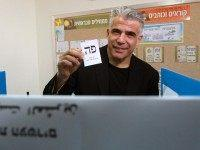 Israeli MP and chairperson of center-right Yesh Atid party, Yair Lapid, prepares to cast his ballot at a polling station, on March 17, 2015 in Tel Aviv. Voting polls opened for unpredictable elections to determine whether Israelis still want incumbent Prime Minister Benjamin Netanyahu as leader, or will seek change …